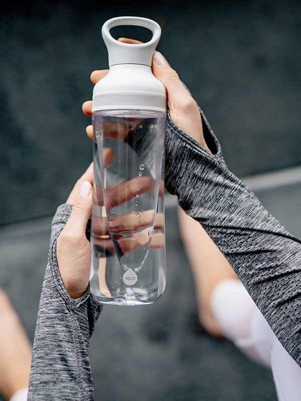 EQUA BPA FREE FLOW water bottle, Freeze, close up of the bottle held in hands, minimal design, no motif, grey color