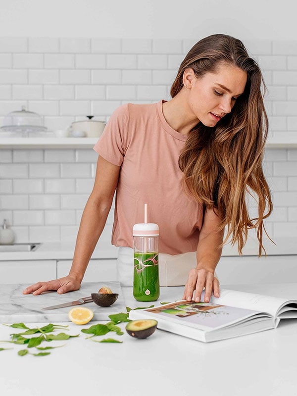 EQUA BPA FREE FLOW 2 in 1 water bottle, Beat, bootle is shown with the straw and smoothie, young woman is browsing smoothie recipes, graphic motif, peach color