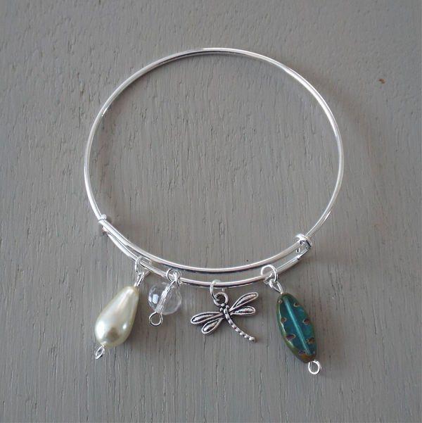 Adjustable silver plated bangle with dragonfly charm and blue green accent