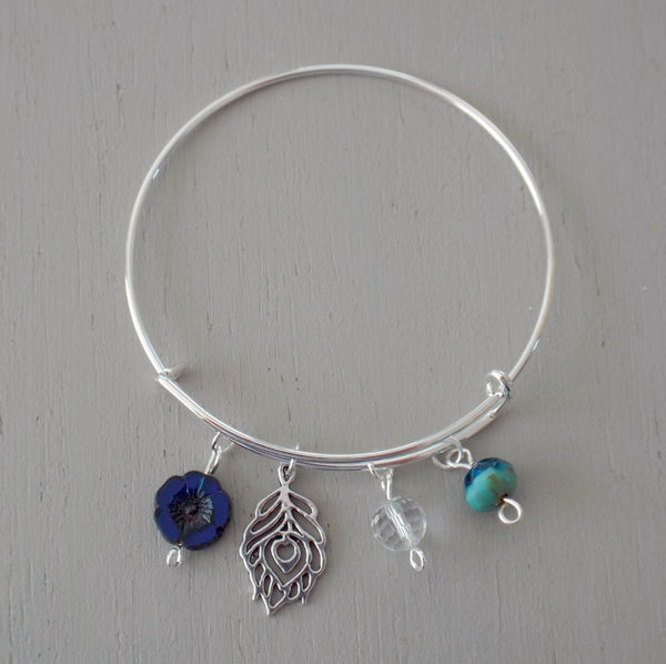 Adjustable bangle with silver plated peacock feather charm, blue / green beads