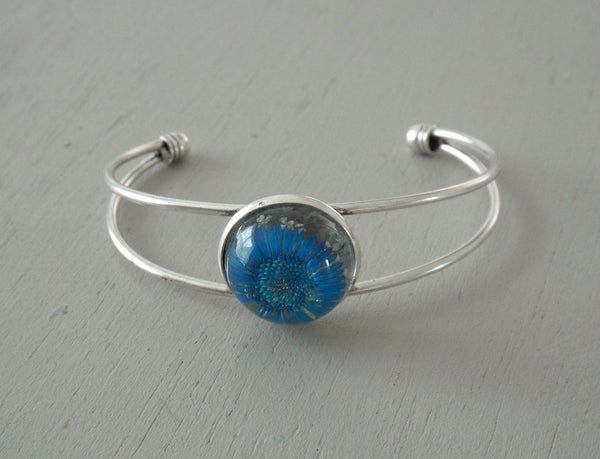 Solid silver plated open bangle with 20mm blue daisy