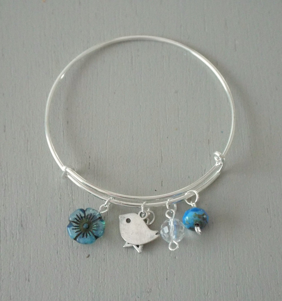 Adjustable silver plated bangle, bird & star charms, blue accents
