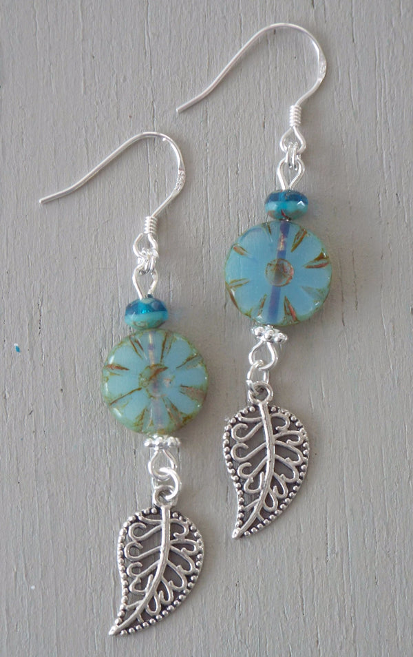 Earrings with silver plated filigree leaf charms, milky aqua wheels