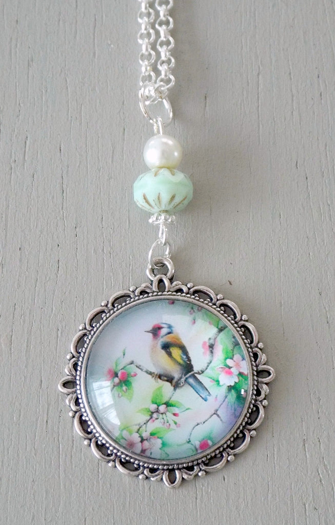 Pendant with 25mm neutral yellow, green bird focal, ornate setting, mint & ivory beads
