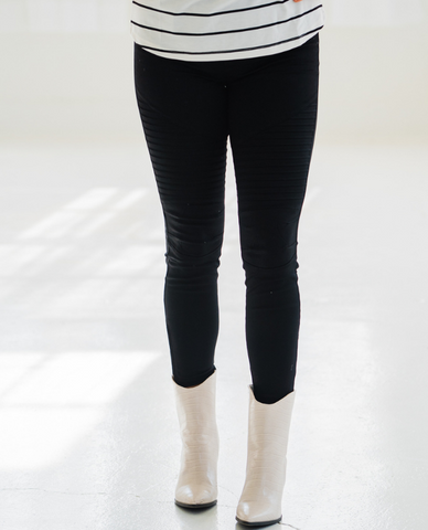 Woman wearing black moto style Jeggings pants with a striped top and white boots.