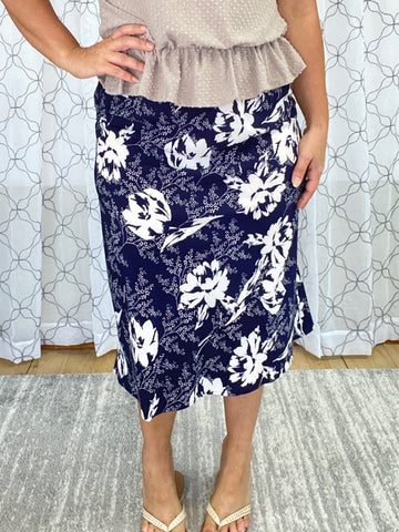 Woman wearing a navy blue and white floral skirt with a taupe blouse and sandals.