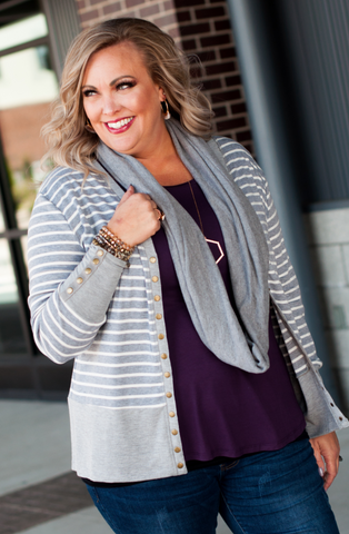 Woman wearing a gray and white striped cardigan with a plum colored top.
