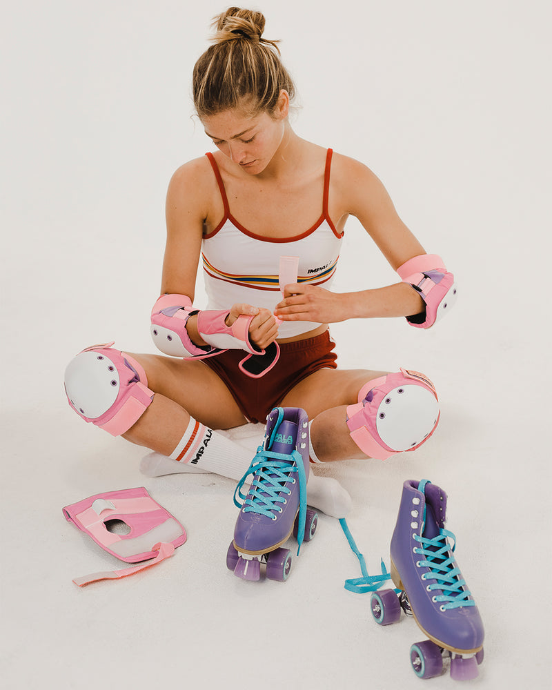 Roller Skater putting on pink Impala adults protective set including wrist guards, knee pads and elbow pads. Safety Equipment for roller skating and skateboarding with Purple Roller Skates