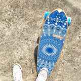 Obfive skateboard with blue mandala print on the top and bottom, blue wheels, silver trunks, suitable for beginners and advanced. Flipped up with white sneakers