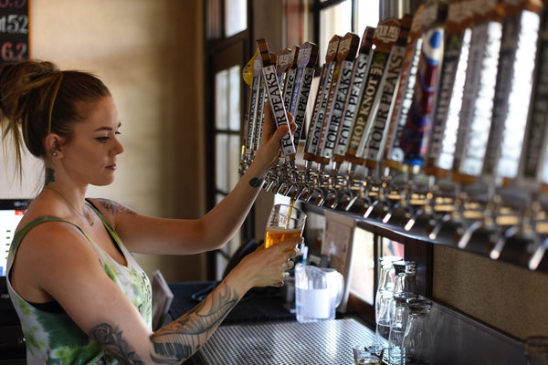 A woman filling beer glass from faucet