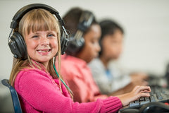 girl with over-ear school headphones on at computer