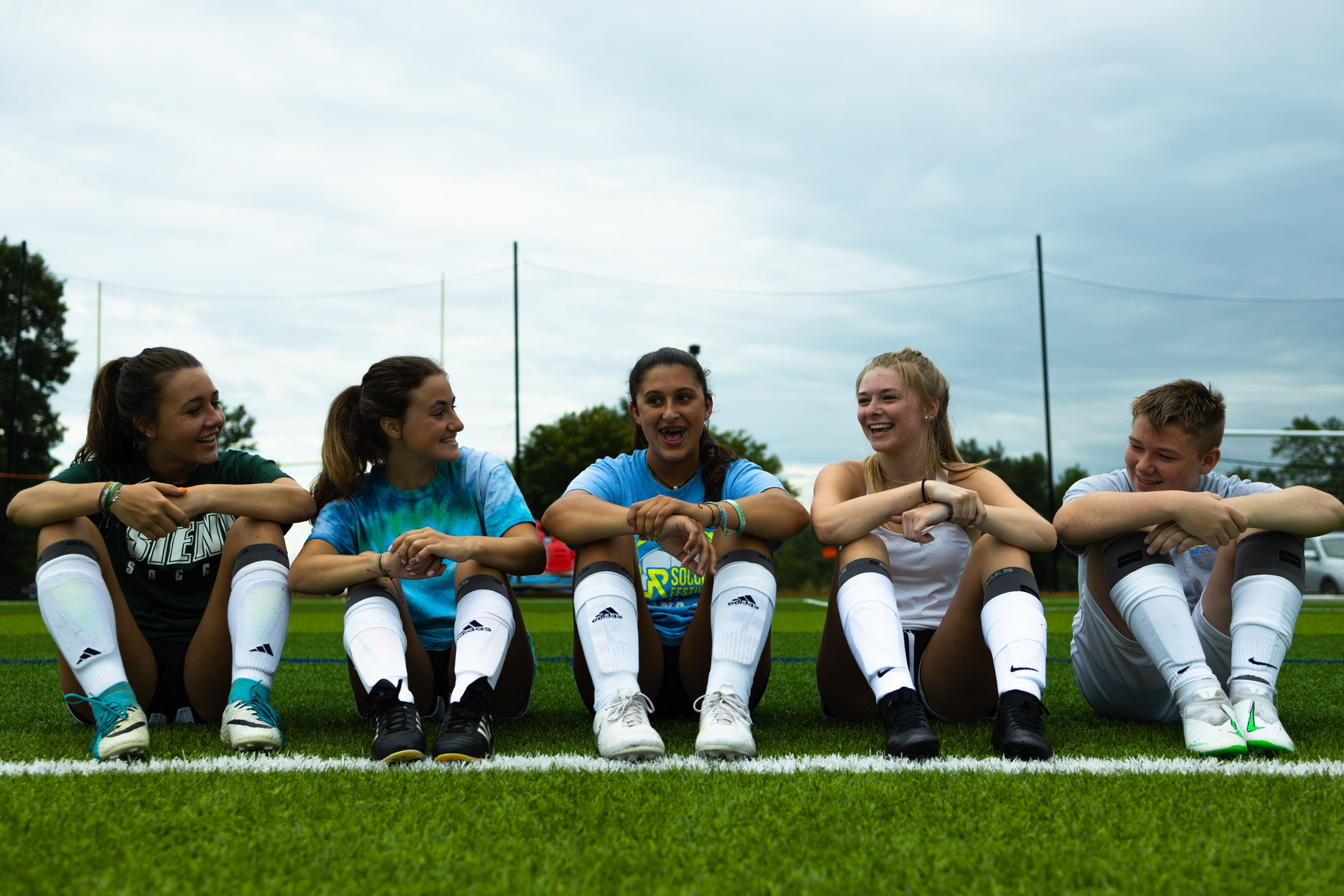 five soccer players wearing soaks under socks sitting on a soccer field