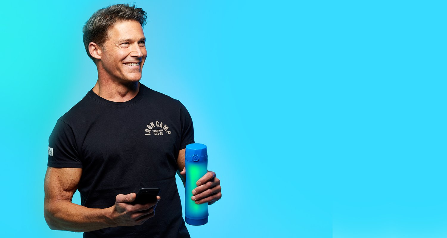 person holding a royal blue hidrate spark 3 bluetooth smart water bottle that is glowing