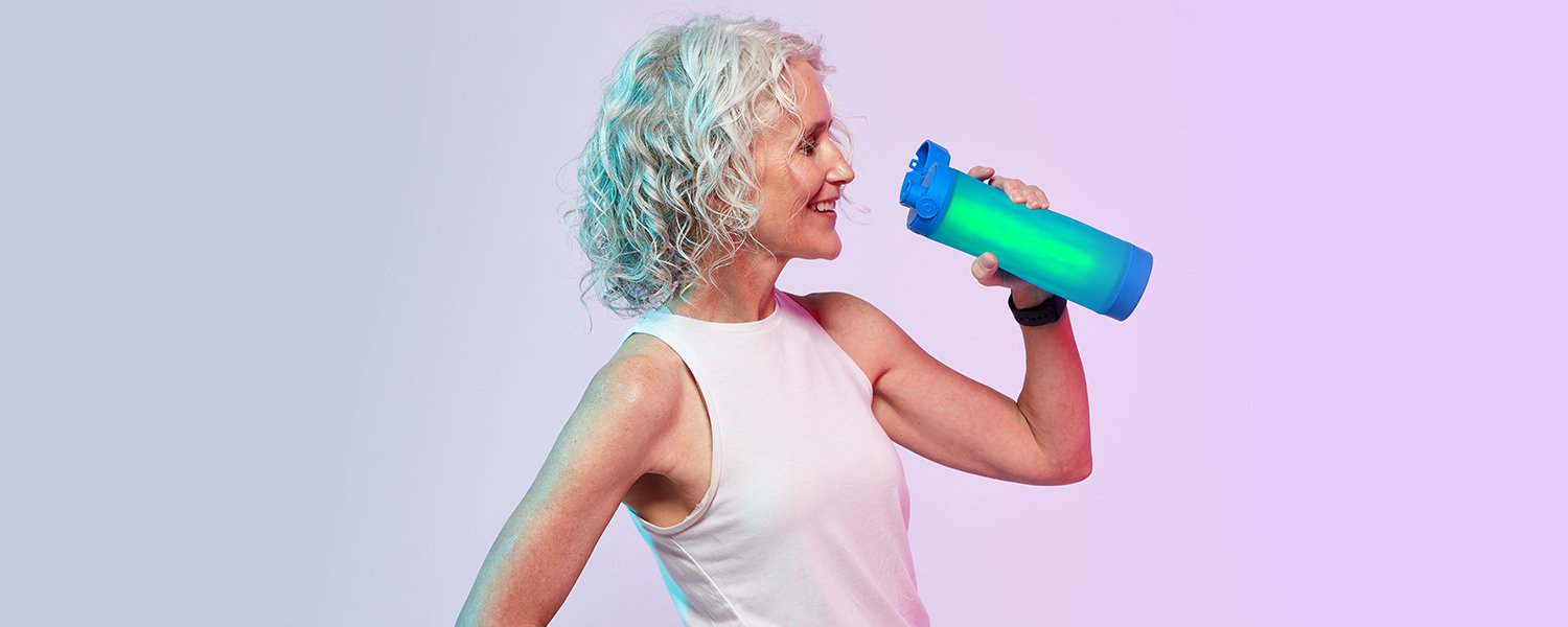 women drinking from a royal blue hidratespark 3 bluetooth smart water bottle that glows.