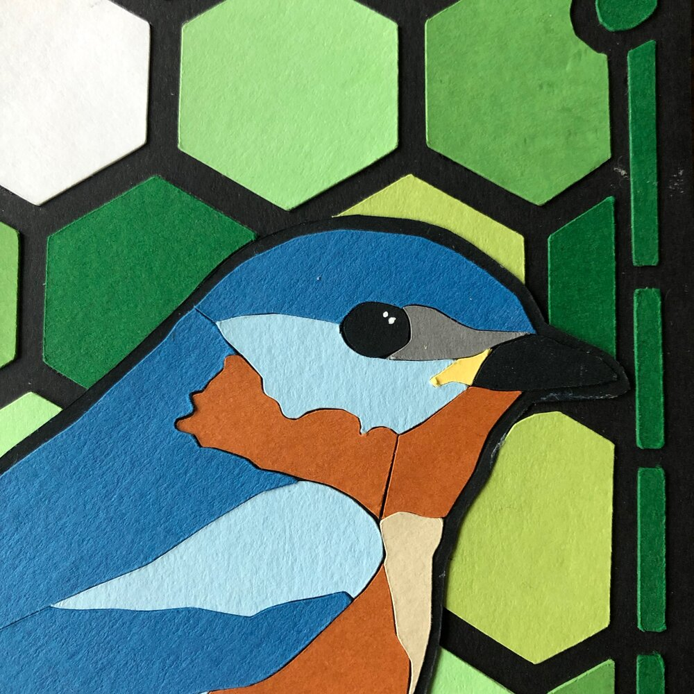 "Each individual piece is hand cut, carved and meticulously assembled. 8"" x 6"" in cut paper. Image in the likeness of a stained glass bluebird, available in the Hudson Valley, New York at Hyperbole."