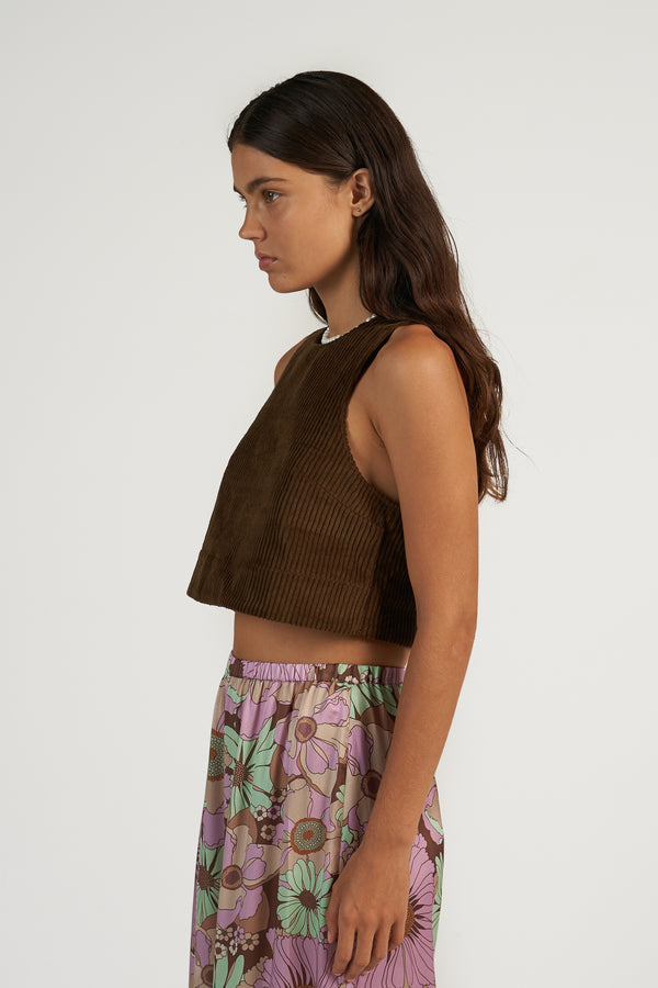 Meet your new summer staple: A corduroy crop top with cutaway armholes, featuring a high, round neck, and a narrow keyhole opening at the back, and an A-line silhouette. Available to shop at Hyperbole in Beacon New York