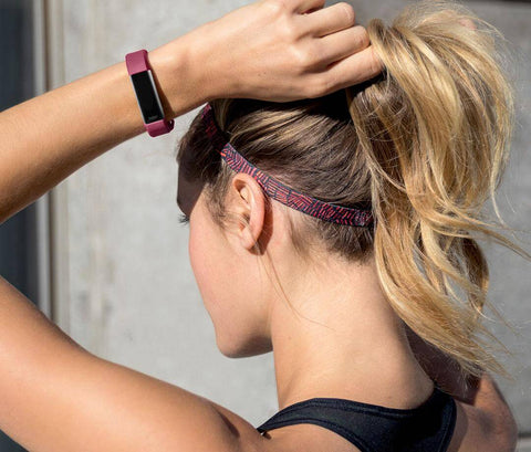 Blonde woman with a pink Fitbit on her arm.