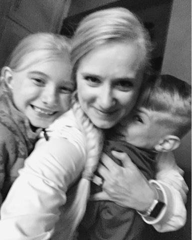 A black and white photo of a woman and two kids hugging.