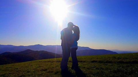 A couple kissing in a field with the sun shining in the background.