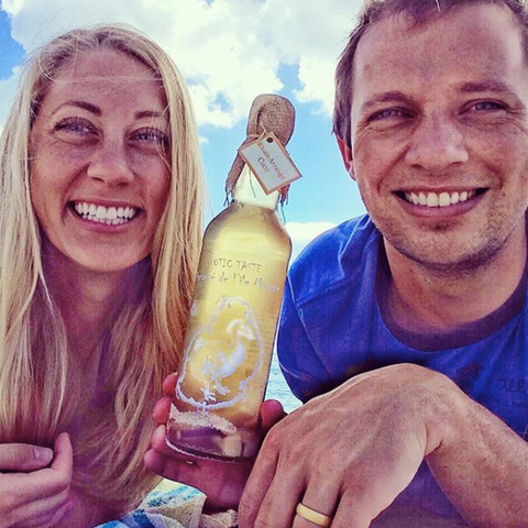 A man and woman smiling at the beach and holding a bottle of alcohol between them.