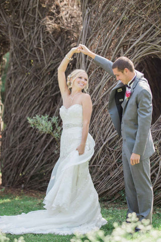 A woman in a white wedding dress dancing with a man in a grey suit.