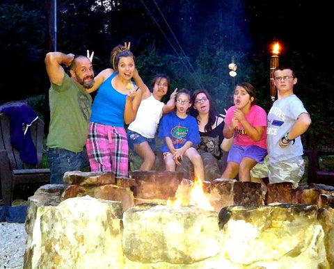 Seven people acting silly by a campfire.