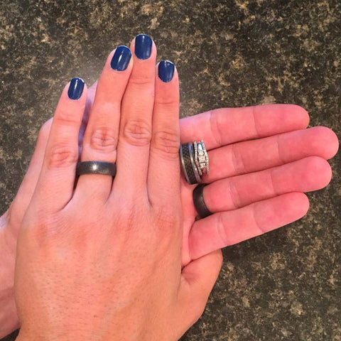 A couple of hands — one with blue fingernails and a silicone ring.