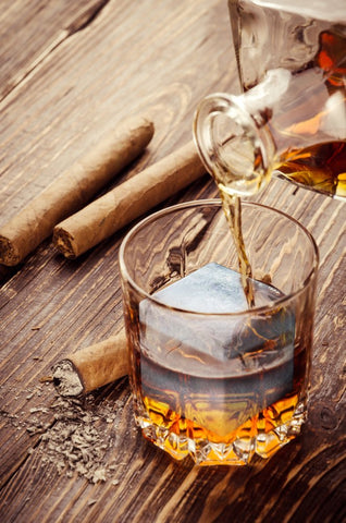 Whiskey being poured into a glass on a table with cigars beside it.