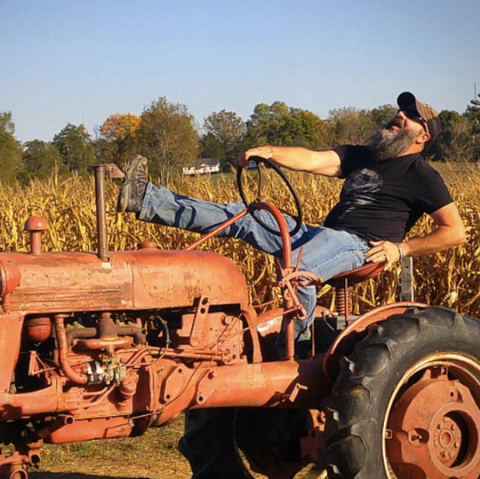 Bearded man leaning back and laughing on a tractor in a corn field.