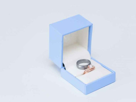 A bronze ring and a silver silicone wedding ring in a baby blue wedding ring box.