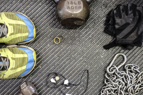 Two wedding bands on the grey floor surrounded by headphones, lifting gloves, a chain, athletic shoes, and weights.