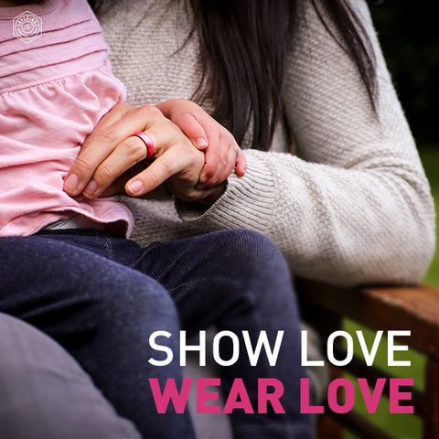 A hand with a pink silicone wedding band on it. Show love. Wear love.