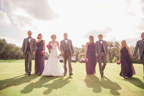 A man and wife walking on a green lawn with their best man and maid of honor.