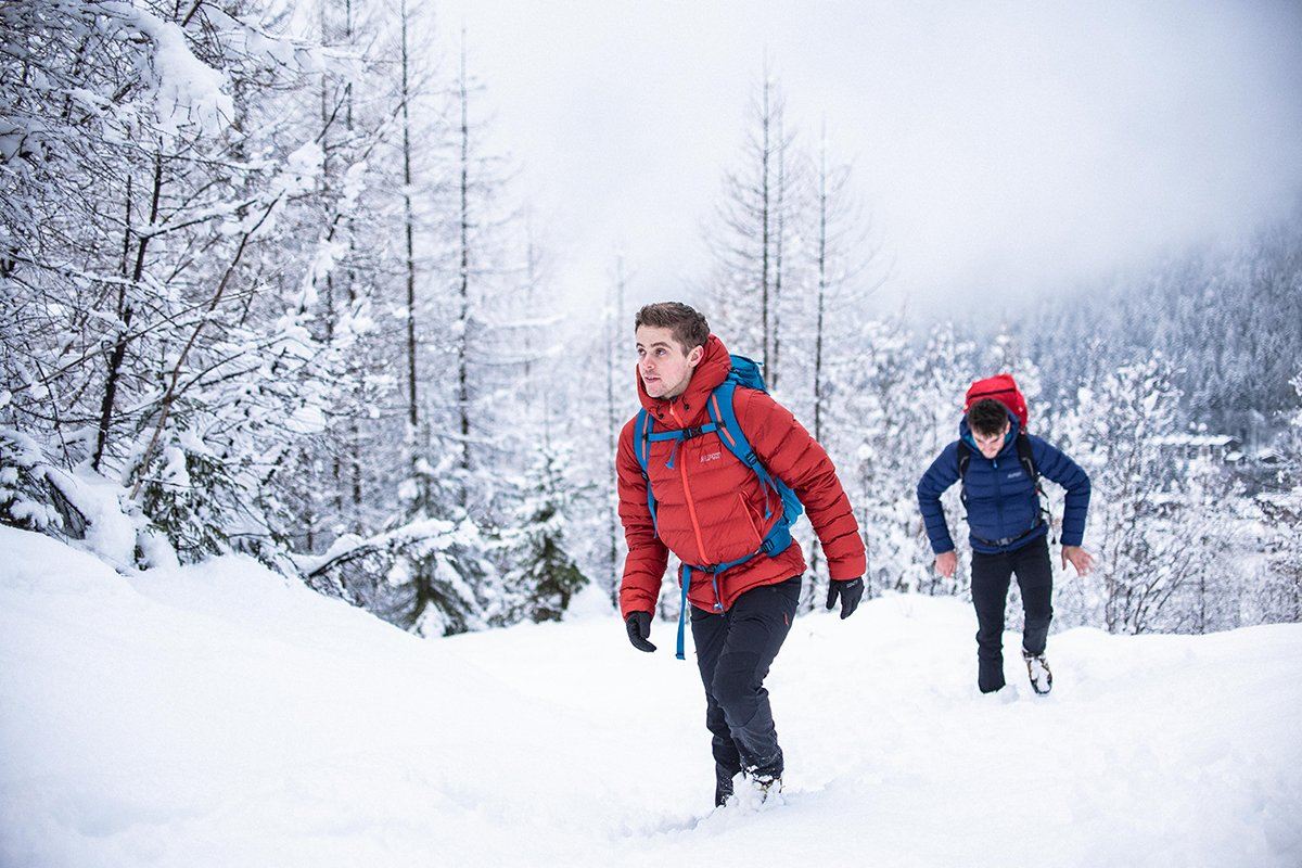 Two people backpacking through snowy woodland in winter