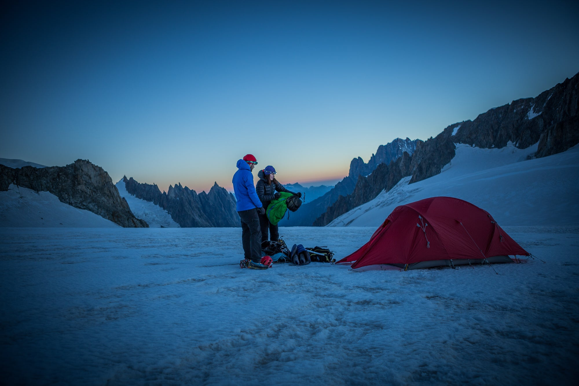 Two people pitching a 4 season mountain tent in the alps