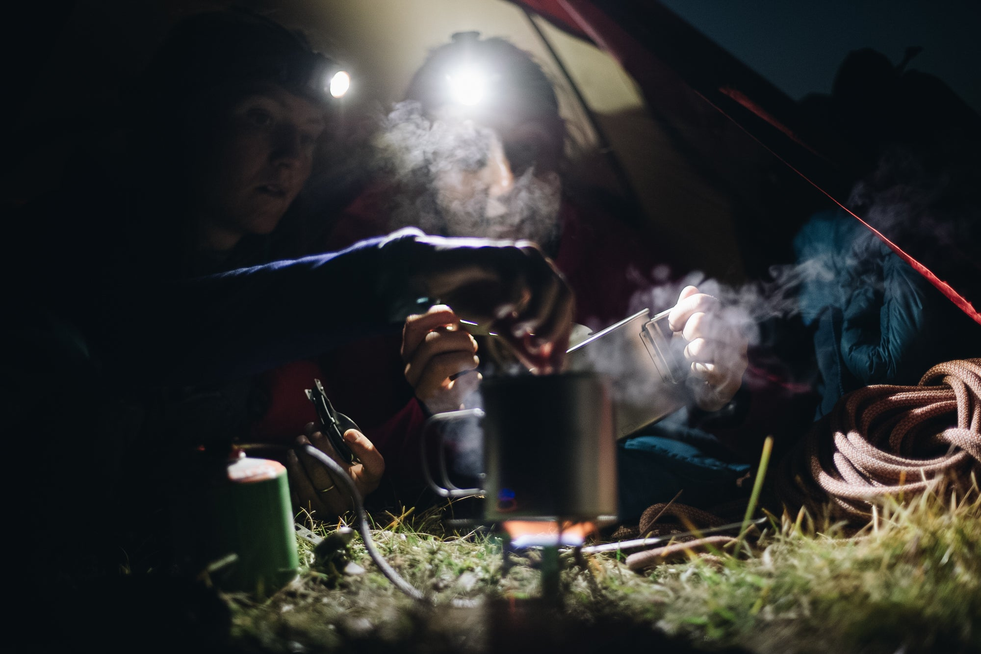 Two people cooking over a mountaineering gas canister stove