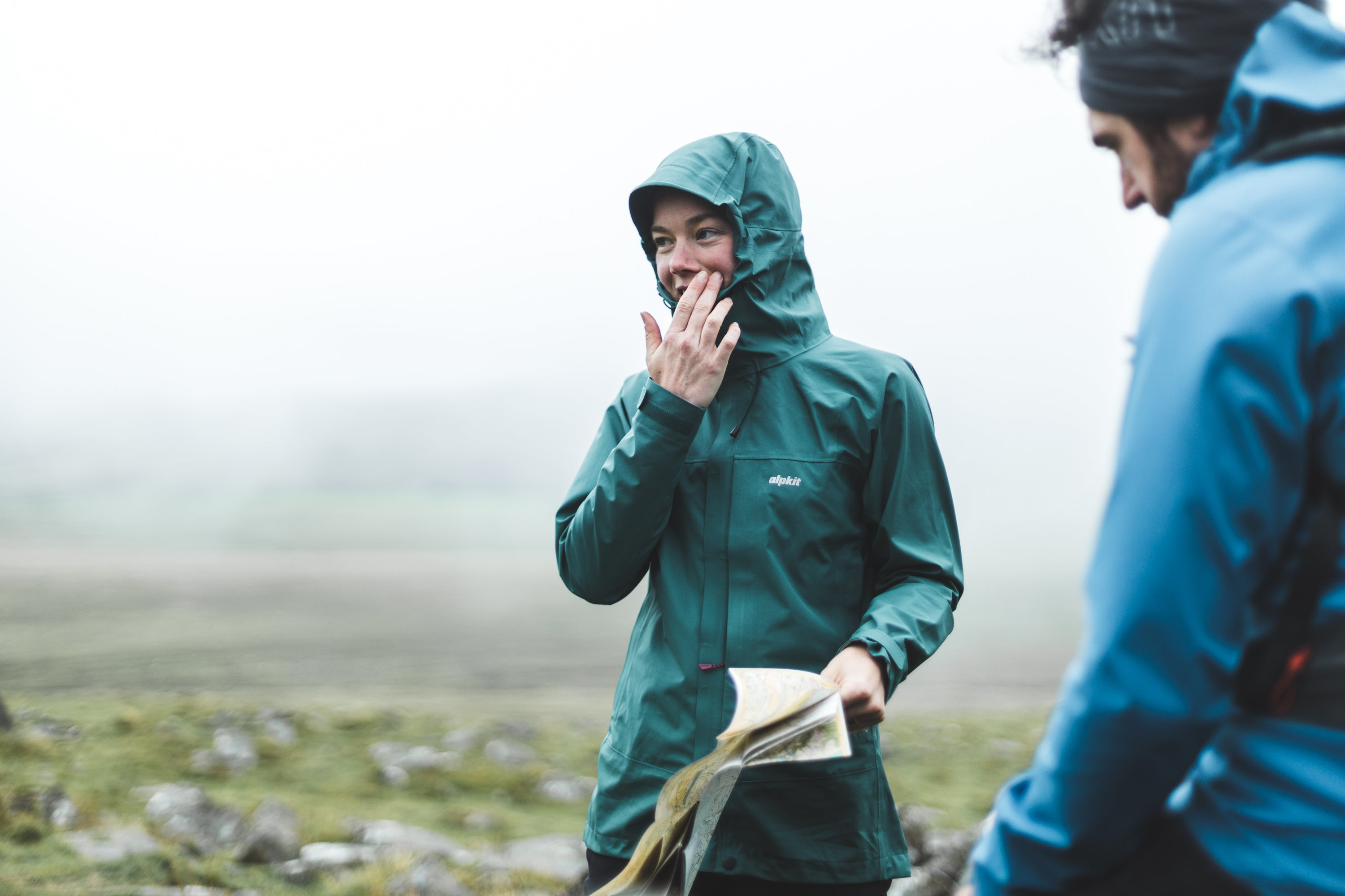 A woman trying to read a map on Dartmoor, wearing a PFC free waterproof jacket