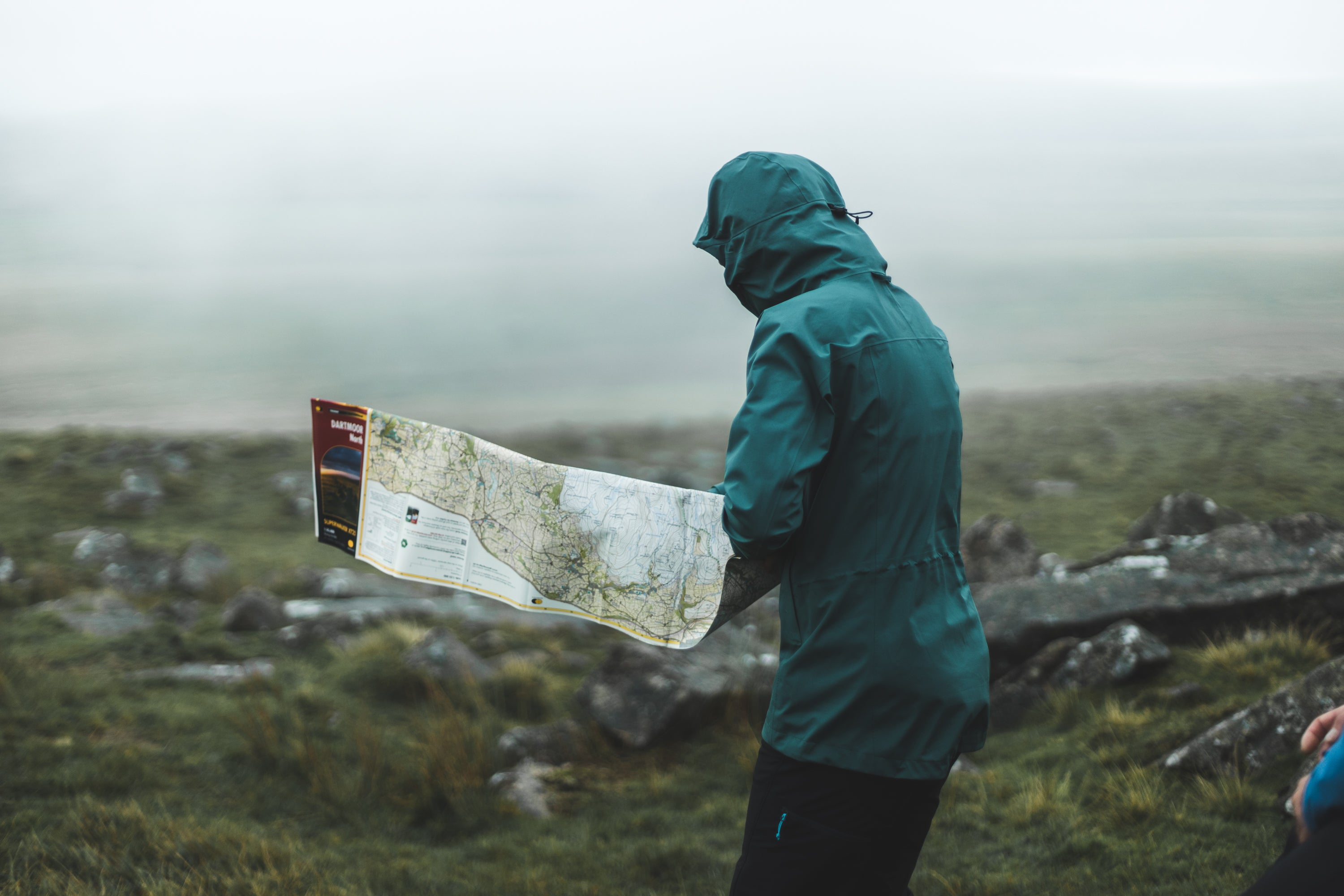 A woman using a Harvey Map on Dartmoor in strong winds, wearing a hillwalking waterproof jacket that's PFC free