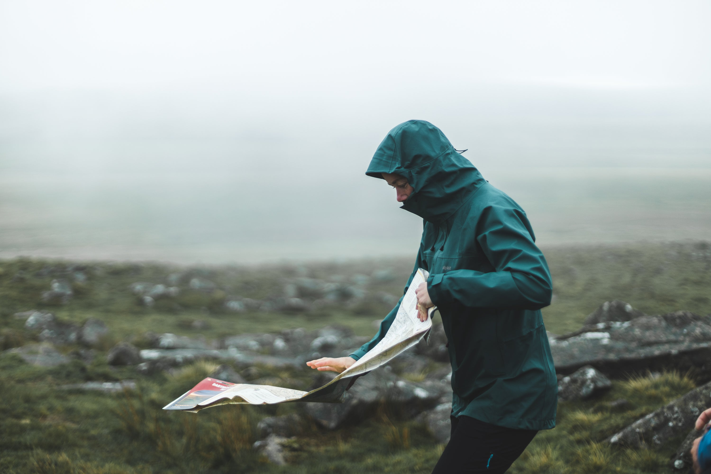 A woman unfolding a map in the rain on Dartmoor in a PFC free waterproof jacket