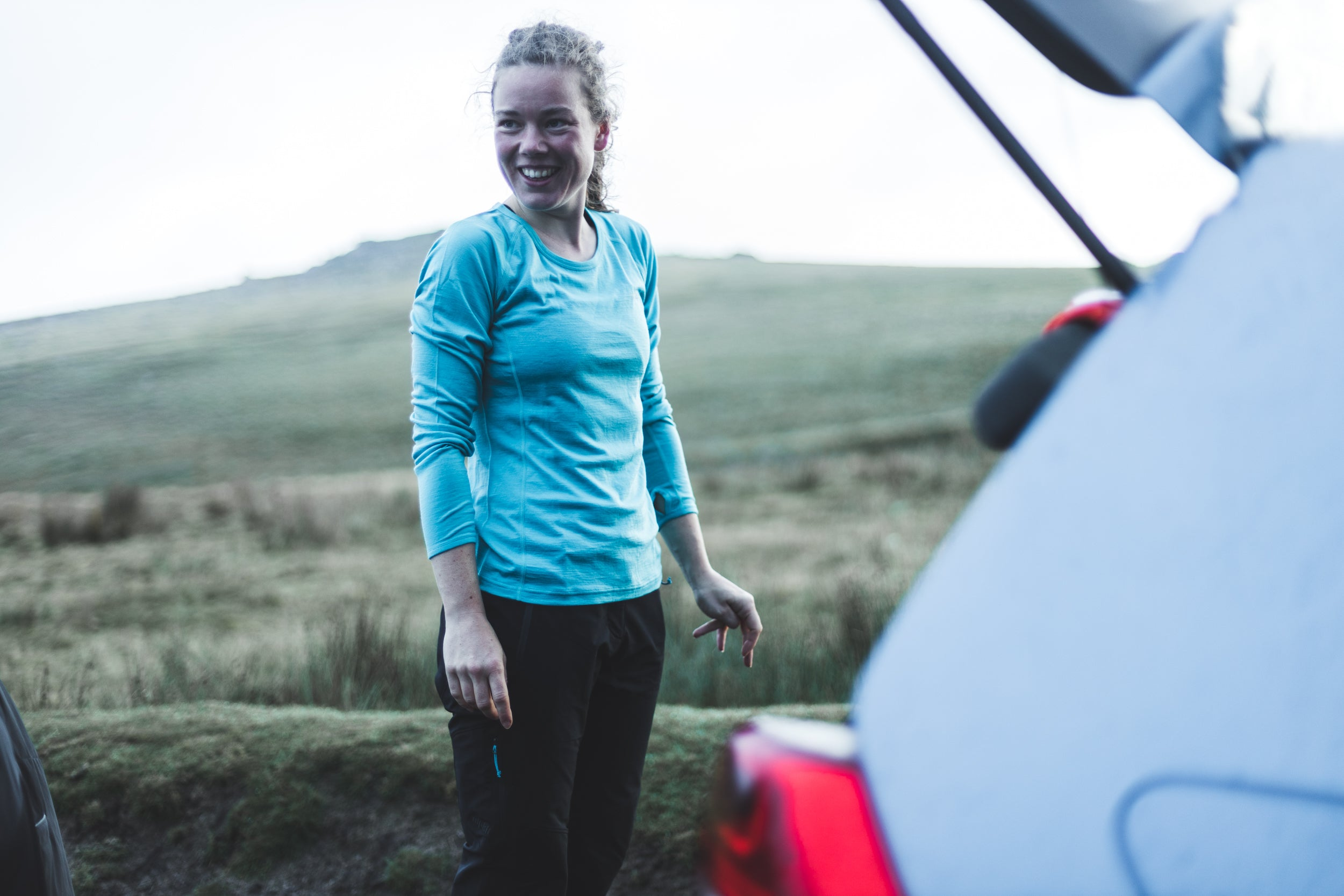 Long sleeved merino base layer getting changed by the car for trail running