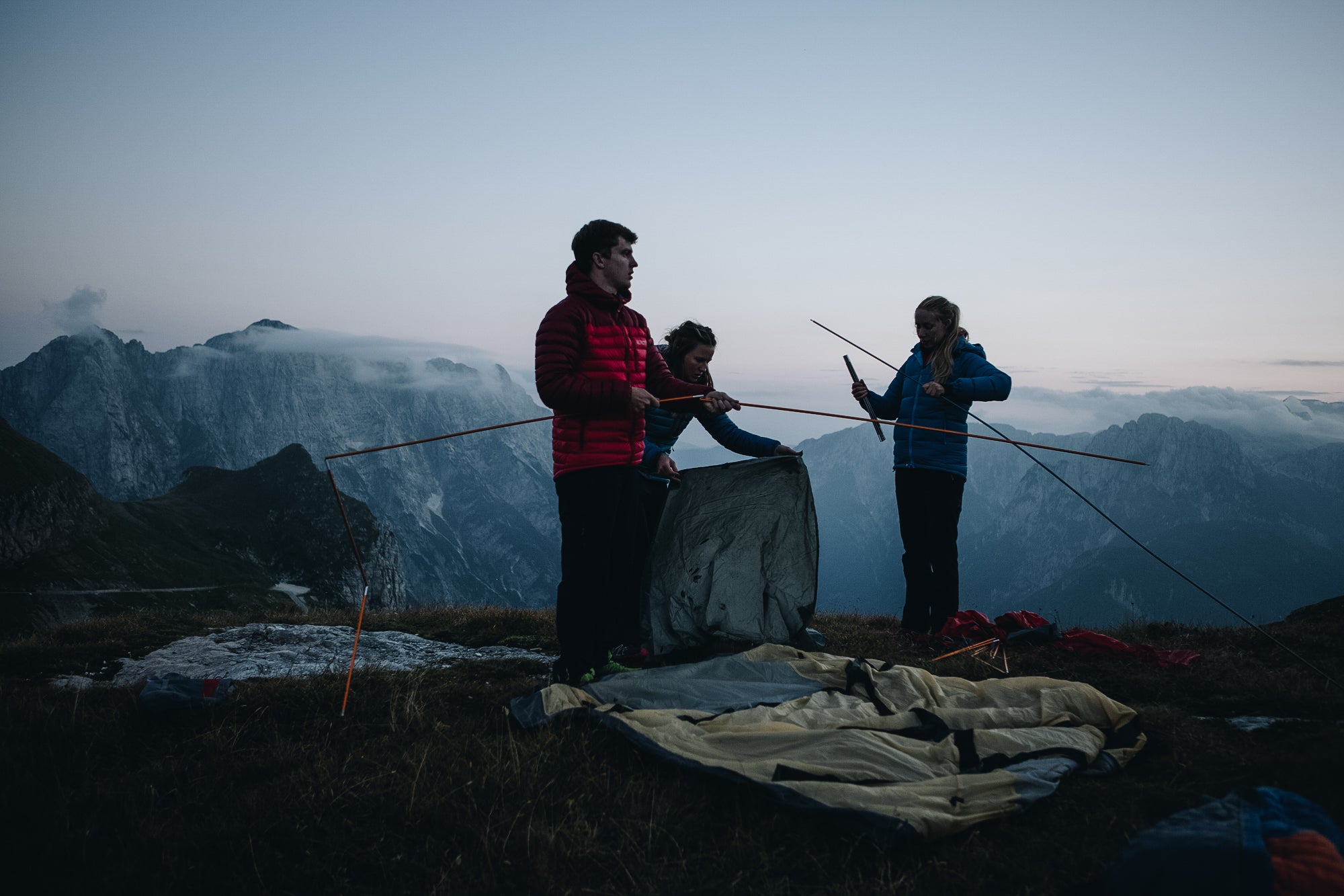 Three people putting the poles together for a 4 season mountain tent in the Slovenian mountains