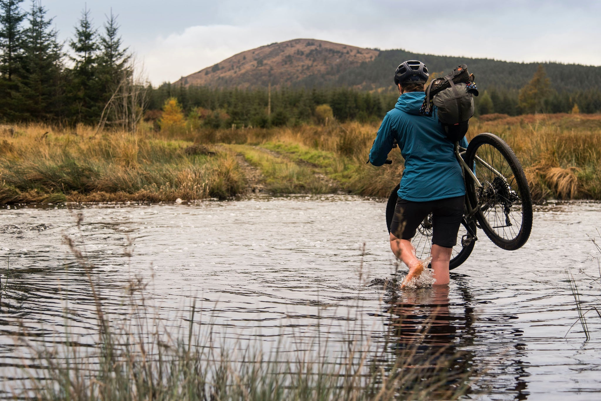 Fording a river while bikepacking in Galloway Forest
