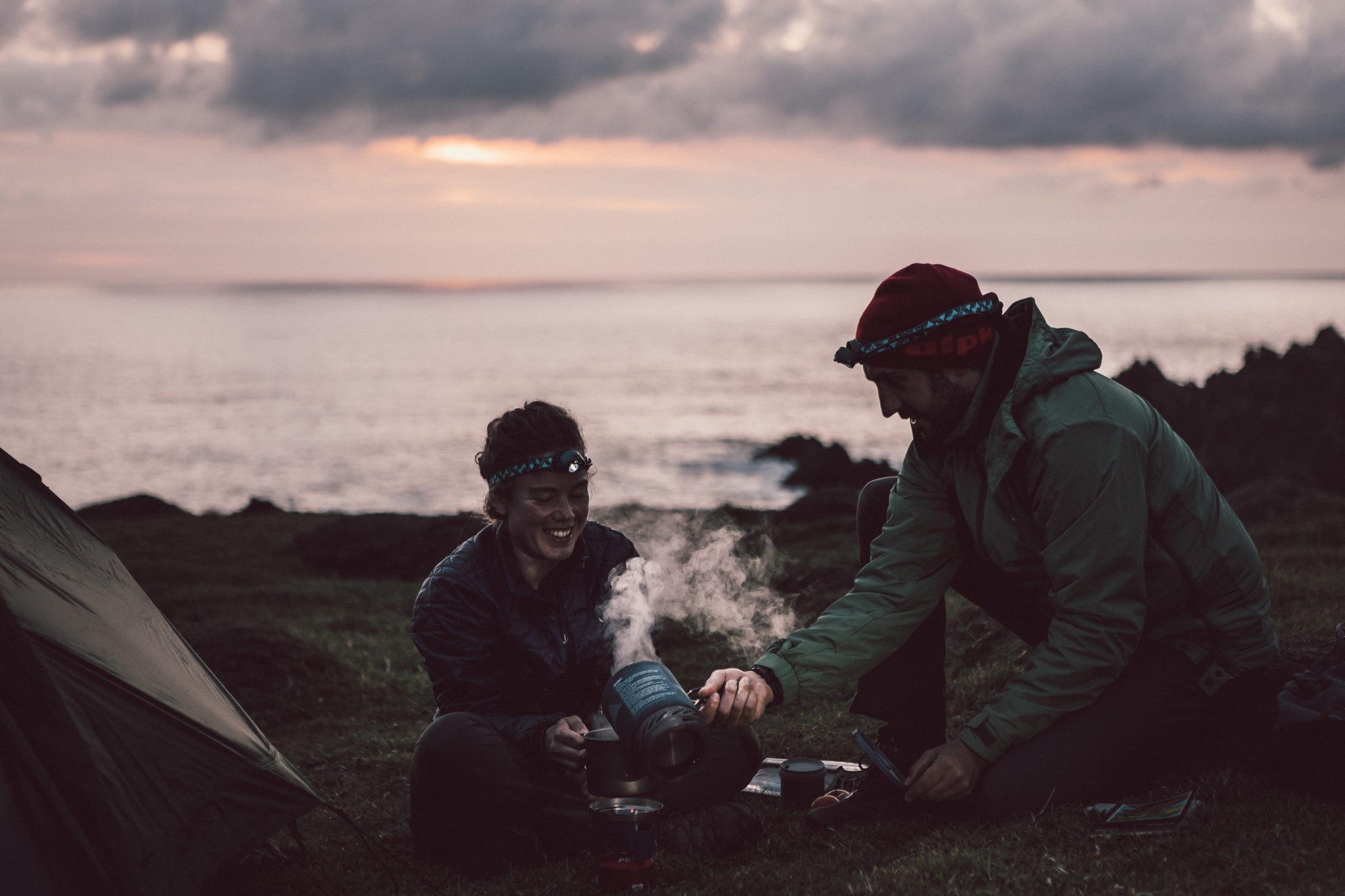 Two people camping and cooking dinner outside their tent on a camping stove