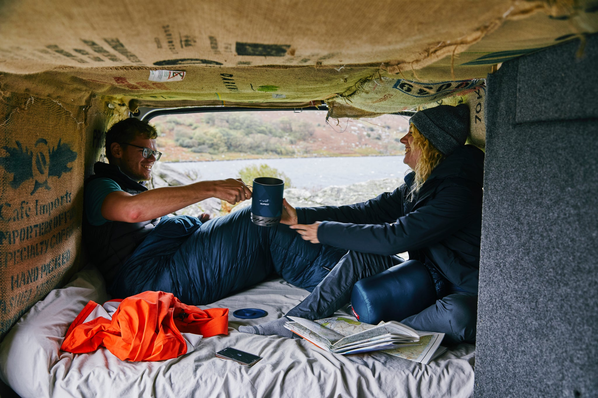 Two people sitting in sleeping bags in a van