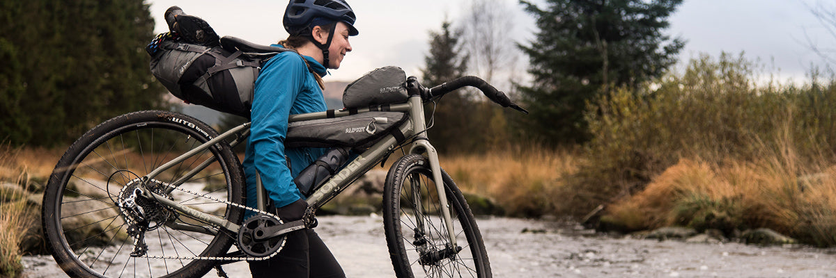 A woman carrying her bikepacking bike with grey bikepacking bags on through a river