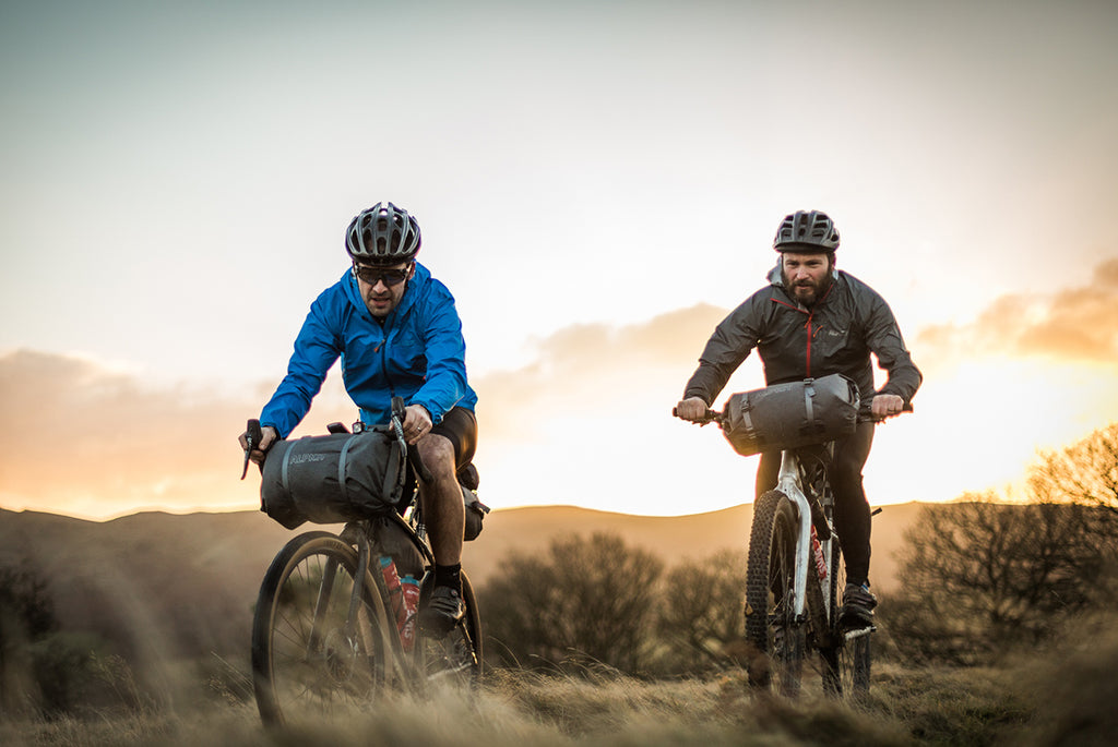 two men riding bikepacking bikes while the sun sets behind them