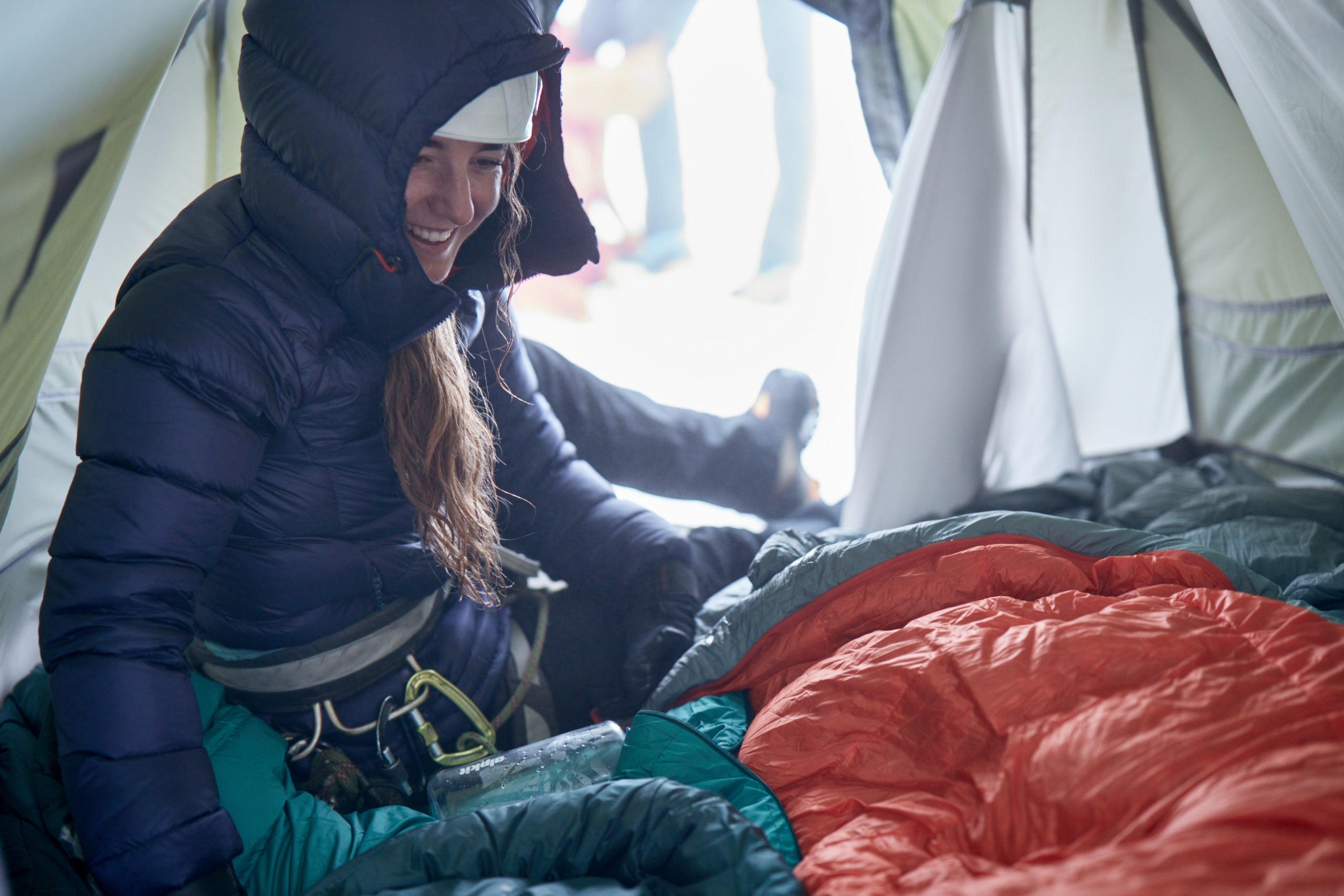 Woman in down jacket in tent with sleeping bag