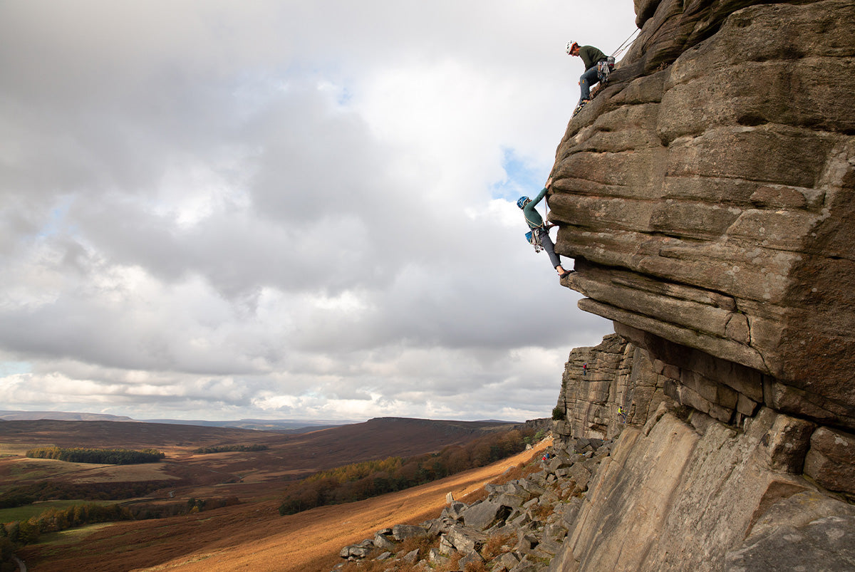 A man and a woman trad climbing on Stanage Edge in the Peak District