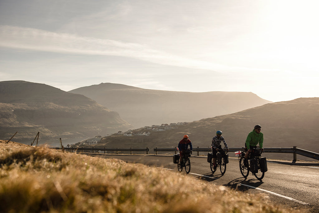 Three friends on touring bikes with panniers in the faroe islands as the sun is setting