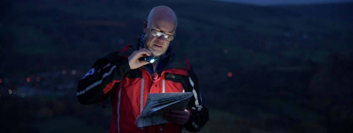 An Edale Mountain Rescue Team member reading a map with a headtorch